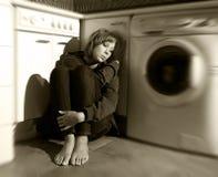 Einsame und kranke Frau, die auf Küchenboden in der Druckkrise und in der Traurigkeit sitzt Lizenzfreies Stockbild