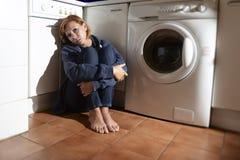 Einsame und kranke Frau, die auf Küchenboden in der Druckkrise und in der Traurigkeit sitzt Stockfotografie