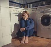 Einsame und kranke Frau, die auf Küchenboden in der Druckkrise und in der Traurigkeit sitzt Lizenzfreies Stockfoto