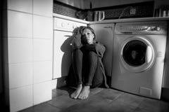 Einsame und kranke Frau, die auf Küchenboden in der Druckkrise und in der Traurigkeit sitzt Stockbild