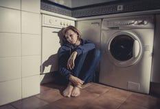 Einsame und kranke Frau, die auf Küchenboden in der Druckkrise und in der Traurigkeit sitzt Stockfotos