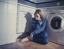 Einsame und kranke Frau, die auf Küchenboden in der Druckkrise und in der Traurigkeit sitzt Lizenzfreie Stockfotos