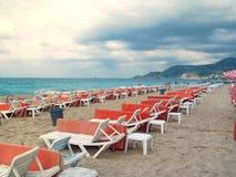 Einsame und leere Sonnenruhesessel durch das Meer warten auf Touristen stockfotos