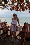 Einsame weibliche Stellung in einem Café auf dem Hintergrund des Meeres Stockfoto