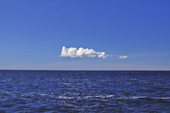 Einsame weiße Wolke über Wasser Lizenzfreie Stockfotos