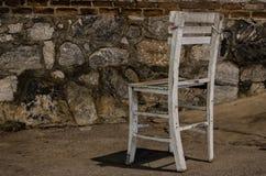 Einsamer alter Stuhl auf Steinhintergrund Lizenzfreies Stockfoto