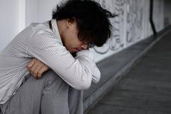 Einsamer deprimierter asiatischer Mann sitzen und umarmen sein Knie auf dem Boden Stockfotos