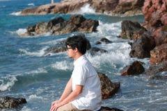Einsamer deprimierter junger asiatischer Mann mit der zufälligen Kleidung, die auf dem Felsen des Seeufers sitzt Lizenzfreies Stockfoto