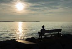 Einsamer einzelner Junge, der auf Bank an der Küste sitzt Stockbild