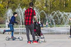 Einsamer einzelner Vaterhippie im karierten roten und schwarzen Hemd mit einem Spaziergänger, der in den Stadtpark geht stockbild