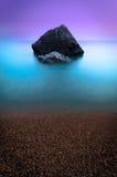 Einsamer Felsen im Meer mit ehrfürchtigen Farben Stockfotografie