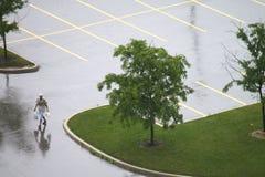 Einsamer Fußgänger im leeren nassen Parkplatz Stockfotos