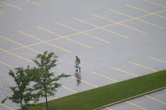 Einsamer Fußgänger in leerem nassem P Stockbild