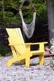 Einsamer gelber adirondack Stuhl Stockfoto
