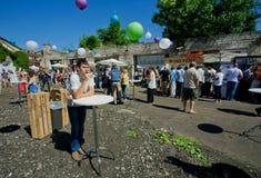Einsamer Getränkwein des jungen Mannes allein auf Festival Stockfotos