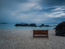 Einsamer Holzstuhl auf dem Strand nach Regen Stockbilder