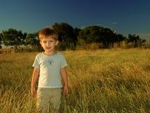 Einsamer Junge auf dem Gebiet Stockfoto