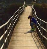 Einsamer Junge, der auf einer Hängebrücke sitzt Lizenzfreie Stockfotografie