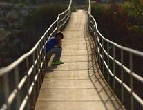 Einsamer Junge, der auf einer Hängebrücke sitzt Stockfotografie