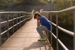 Einsamer Junge, der auf einer Hängebrücke sitzt Stockfoto