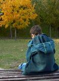 Einsamer Junge sitzt auf einer Bank Lizenzfreie Stockfotografie