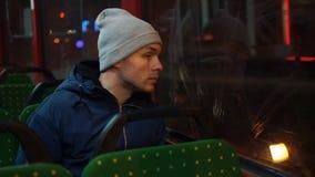 Einsamer junger Mann reitet in eine Tram in der Nacht stock footage
