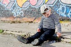 Einsamer kleiner Junge, der an sitzt Stockfoto