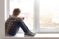 Einsamer kleiner Junge nahe Fenster zuhause lizenzfreies stockfoto