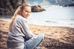 Einsamer lächelnder Frauentourist, der auf Strand am bewölkten Tag sitzt und Kamera betrachtet stockbilder