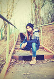 Einsamer Mädchenjugendlicher im Hut, der auf Treppe und traurigem Herbst sitzt Lizenzfreie Stockbilder