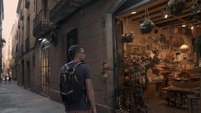 Einsamer männlicher Tourist schlendert auf die alte Straße und schaut auf Souvenirladen stock video
