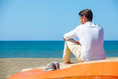 Einsamer Mann auf dem Strand über einem Boot, welches das Meer betrachtet stockbilder