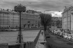 Einsamer Mann, der auf die Bank von Neva-Fluss in St Petersburg geht Gegen die Flusskonzeption Leere Tabelle mit einem Raum für T Stockbild