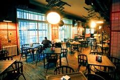 Einsamer Mann, der im enormen Raum der leeren Bar mit modernem Design sitzt Stockfoto