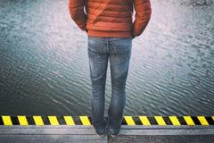 Einsamer Mann in der roten Jacke steht am See Stockfoto