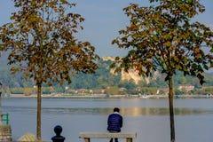 Einsamer Mann, der zwischen zwei Bäumen auf einer Bank sitzt und den See betrachtet Im Abstand können Sie die Insel sehen, auf de Lizenzfreies Stockbild