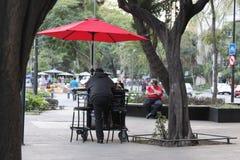 einsamer Mann unter dem roten Regenschirm in Mexiko lizenzfreies stockbild