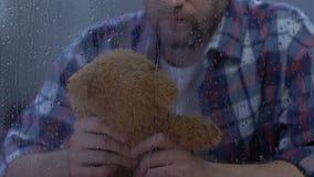 Einsamer Mannholdingteddybär hinter regnerischem Fenster, vermisstes Kind nach Scheidung stock footage
