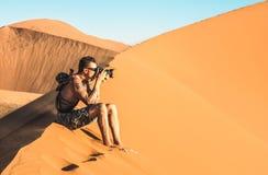 Einsamer Mannphotograph, der auf Sand an Düne 45 in Sossusvlei Namibia sitzt stockbild