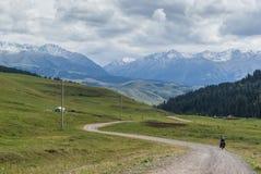 Einsamer Radfahrer in den Bergen von Kirgisistan Stockfotografie
