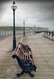 Einsamer regnerischer Pier des leeren Stuhls Stockfoto