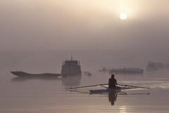 Einsamer Rower auf Fluss am nebelhaften Sonnenaufgang lizenzfreies stockfoto