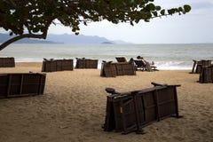Einsamer sandiger Strand mit Strandstühlen und -regenschirmen nahe dem Meer Stockbild