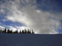 Einsamer Skifahrer auf einer Kante einer Skisteigung Stockfoto
