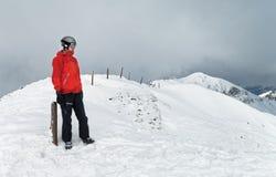 Einsamer Snowboarder, der die Ansicht bewundert stockbilder