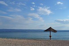 Einsamer Sonnenregenschirm am Strand Stockfotografie