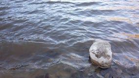 Einsamer Stein im See Stockfotos