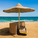 Einsamer Strand mit geflochtem Sonnenregenschirm stockfoto