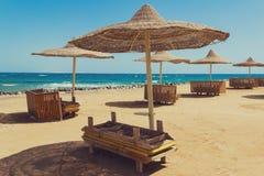 Einsamer Strand mit geflochten Sonnenschirmen stockfotografie