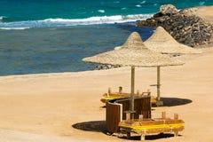 Einsamer Strand mit geflochten Sonnenschirmen lizenzfreies stockfoto